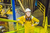 Young Woman In A Yellow Work Uniform, Glasses And Helmet In Industrial Environment, Oil Platform Or  poster