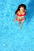 Woman relaxing in swimming pool. Beautiful gorgeous young bikini model bathing in blue swimming pool