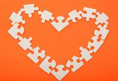 Puzzles In The Shape Of A Heart On An Orange Background.