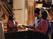 picture of soliciting  - Female receptionist giving room key to couple - JPG