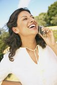 Woman laughing while talking on cell phone