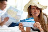 Feliz mujer con sombrero mostrando los billetes de avión