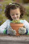 Girl planting flowers in pot