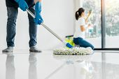 Young Housekeeper Cleaning Floor Mobbing Holding Mop And Plastic Bucket With Brushes, Gloves And Det poster