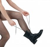 stock photo of grommets  - Girl in sexy pantyhose lacing her army - JPG