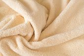 Fluffy Beige Towel Background, Close-up. Gentle Baby Pastel Fabric With Waves And Folds. Folded Tend poster