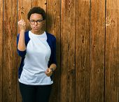 Young beautiful african american woman wearing glasses over isolated background angry and mad raisin poster