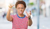 Beautiful young african american woman wearing glasses over isolated background Shouting frustrated  poster