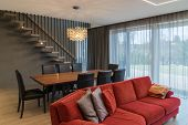 Dining Area And Living Room In The Interior Of Modern House. Cozy Home Interior With Red Sofa, Dinin poster