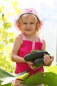 little girl with a zucchini in the hands