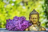 Golden Antique Buddha Statue. Buddha Statue And Blooming Lilac Buddha Head poster
