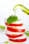 Fresh salad with mozzarella, tomato and basil with olive oil pouring from bottle