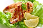 Grilled chicken breast with fresh lettuce and lemon
