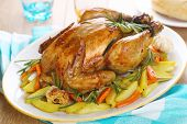 Whole roasted chicken with vegetables on a white plate