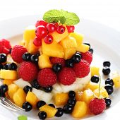 Salad with fresh fruit and berries on  white plate