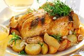 Whole roasted chicken with potatoes and provencal herbs