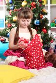 A little girl gets gifts from bag of Santa Claus in festively decorated room