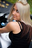 stock photo of crotch-rocket  - A pretty blonde girl posing on a motorcycle.