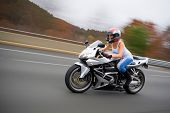 foto of crotch-rocket  - A pretty blonde girl in action driving a motorcycle at highway speeds.