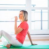 Pretty young woman refreshing during workout at home