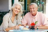 Senior Couple Enjoying Snack At Outdoor Cafe