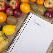 Fruits and book on wooden surface