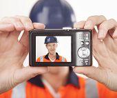 Carpenter taking self portrait with digital camera