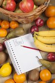 Various fruits in basket with pencil and book