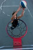 Young basketball player on the street going to the hoop. Great angle from above. Focused on the bask