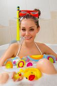 A young beautiful woman is enjoying a bath in mask with snorkel. Playing with his rubber ducky.