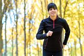 Brunette Sport Woman Running With Trees On Background