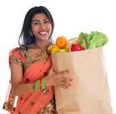 Happy grocery shopper. Portrait of beautiful traditional Indian woman in sari dress holding paper shopping bag full of groceries isolated on white.