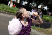 picture of candy cotton  - Girl is eating cotton candy in the park - JPG