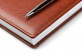 Brown leather notebook with pen on white