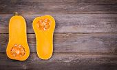 Sliced butternut squash over old wood background with intentional vignette