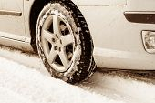 stock photo of slippery-roads  - Close up of a cars tires on a snowy road  - JPG