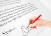Hand writing personal signature on a legal paper
