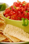 Freshly made tortilla chips with a corn and tomatoe salsa with limes