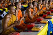 A Row Of Praying Monks In Thailand