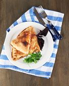 Pizza calzones on plate on napkin on wooden table