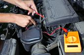 stock photo of electricity meter  - Auto mechanic uses multimeter voltmeter to check voltage level in car battery - JPG