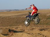 foto of moto-x  - a motocrosser takes flight in the late afternoon and shows off for his friends mid - JPG