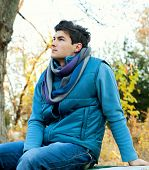 Young stylish man sitting in autumn park.