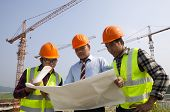 Architects At A Construction Site Looking At Blueprint