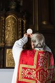 Consecration during an old-fashioned catholic mass in a 17th century church interior