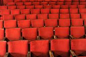 Rows Of Theater Seats With Wooden Arm Rests
