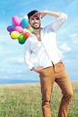casual young man holding balloons outdoor and looking far away while holding a hand above his eyes a