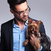 casual young man holding a puppy and looking at it. on gray background