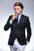 image of exhale  - young business man with a hand in his pocket is exhaling smoke from the cigarette he is holding while looking at the camera - JPG