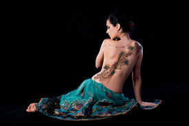 picture of female peacock  - Profile portrait of beautiful brunette woman sitting on the ground with her back to the camera - JPG
